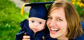 baby dressed in graduation cap and gown with happy mom
