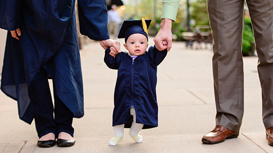 Baby in cap and gown holding parents' hands