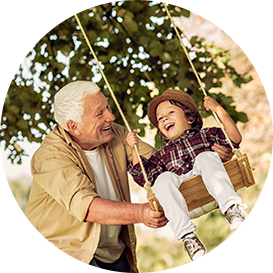 grandfather pushing his grandson on a swing