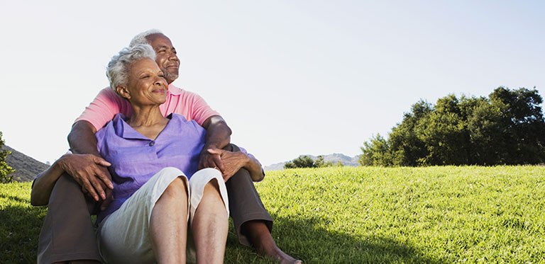 older couple sitting together in a field