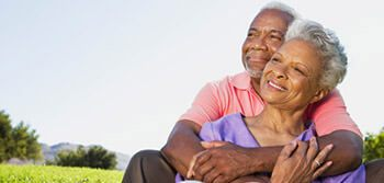 senior couple sitting on grass, hugging