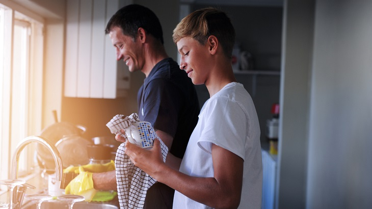 Cash Value Life Insurance – Father and son washing dishes together
