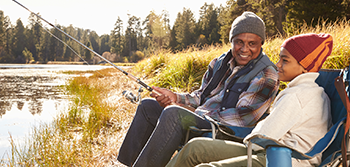 Whole Life Insurance: Senior man and grandson fishing and smiling
